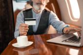 Oříznutý pohled na kreditní kartu v ruce podnikatele pomocí notebooku v blízkosti poháru v letadle