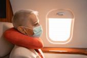 Podnikatelka v lékařské masce a krku polštář sedí v tryskáči