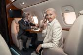 Lächelnde Geschäftsfrau spricht auf Smartphone und blickt in Kamera in der Nähe verschwommener Geschäftsmann im Flugzeug