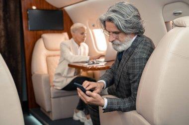 Businessman using smartphone near blurred businesswoman in plane stock vector