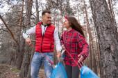 boldog pár szemeteszsákkal szemetet szednek fel markoló szerszámokkal az erdőben