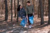 boldog fiatal nő és férfi szemeteszsákokkal szemetet szednek fel markoló szerszámokkal az erdőben