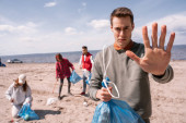 young man showing stop gesture near blurred group of volunteers picking up trash, ecology concept