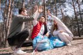 veselí dobrovolníci dávat vysoké pět v blízkosti pytle na odpadky v lese