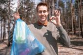 boldog fiatalember kezében kék szemetes zsák és mutatja rendben jel az erdőben