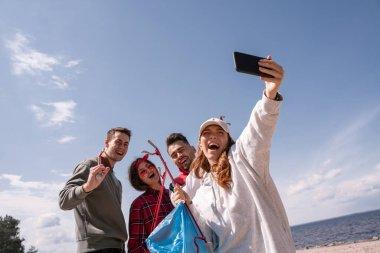 Neşeli kadın arkadaşlarıyla birlikte çöp toplarken selfie çekiyor.