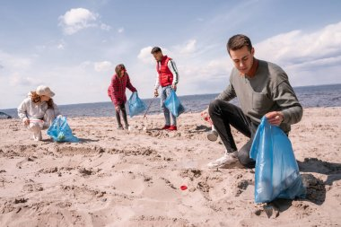 Young man holding trash bag and collecting rubbish on sand near group of volunteers stock vector