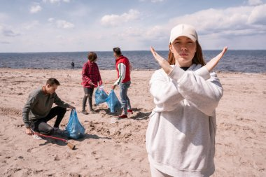 young woman in cap showing stop gesture near group of volunteers picking up trash, ecology concept