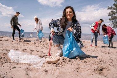 Gönüllüler grubunun yanında çöpleri toplayan mutlu genç bir kadın.