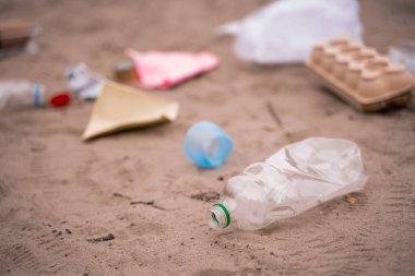Plastic bottle near blurred trash on sand stock vector