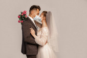 side view of bride and groom in protective masks standing face to face isolated on grey