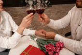 partial view of young couple clinking wine glasses while holding hands in cafe