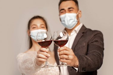 Selective focus of glasses with red wine in hands of newlyweds in medical masks isolated on grey stock vector