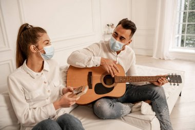 Couple in safety masks playing musical instruments in living room stock vector