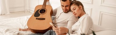 man with acoustic guitar looking at mbira in hands of girlfriend, banner