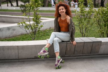 happy and curly roller skater smiling at camera on bench in skate park