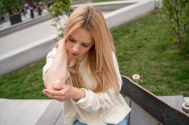 blonde woman applying adhesive plaster on injured elbow near skateboard on bench