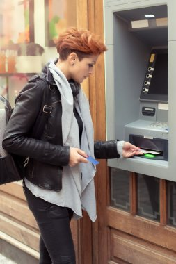Business woman taking money from ATM
