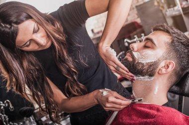 Female barber shaving a client