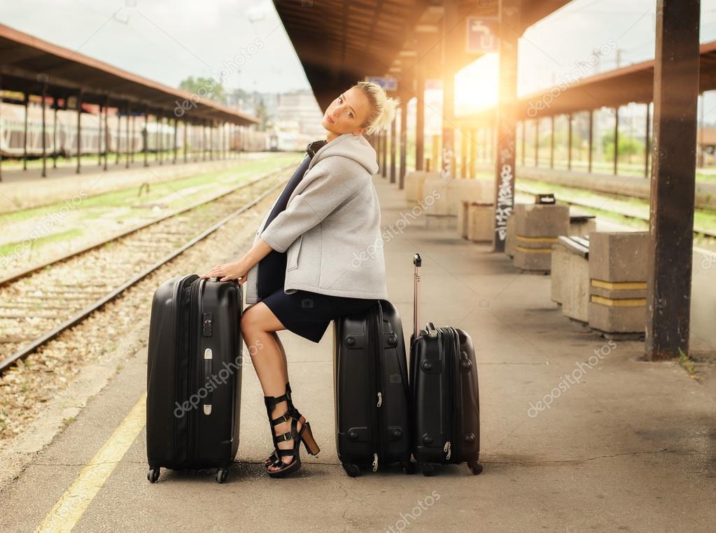 mujer elegante sentado en maletas y esperando al tren u foto de stock