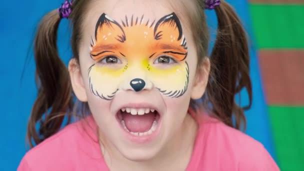 aquagrim a gyermek arcán. Portré egy lányról, akinek Chanterelle minta van az arcán. Szórakozás az ünnepekre. Tetoválás egy kisgyereknek. A gyermekek kreativitása.