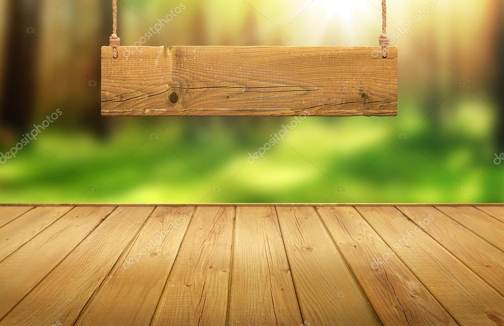 Wood table with hanging wooden sign on green forest blurred background