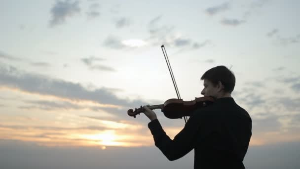 Violinist puts musical instrument on his shoulder and begins to play.
