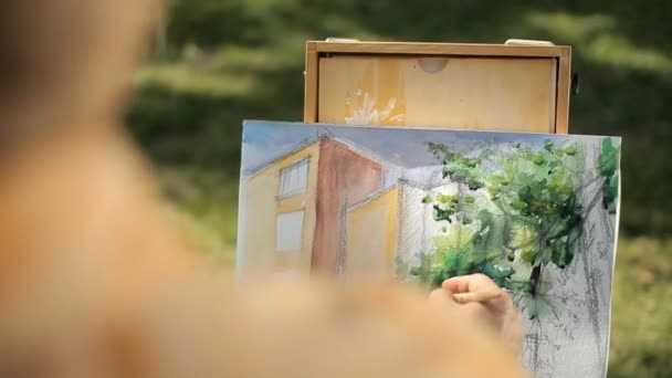 Artist painting a house and a tree from nature. Plein air.
