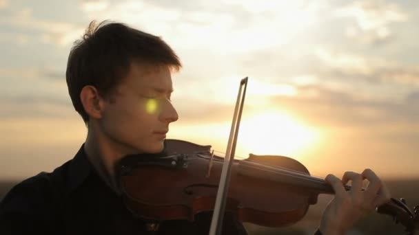 A young violinist in a black shirt, playing on the roof.