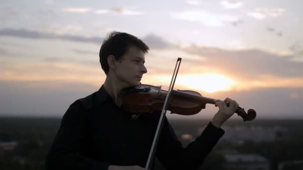 Violinist puts musical instrument on his shoulder and begins to play