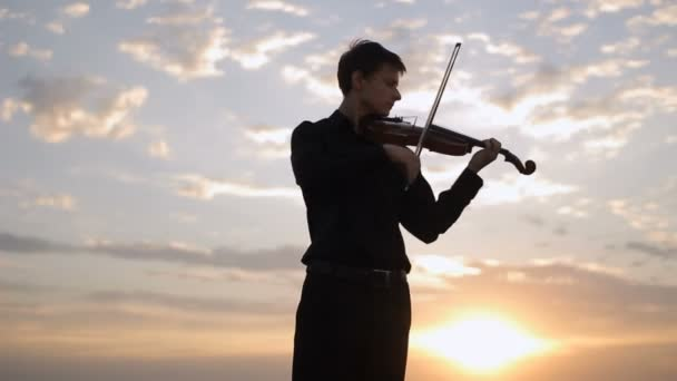 Violinist playing at sunset on the roof. Music, art.