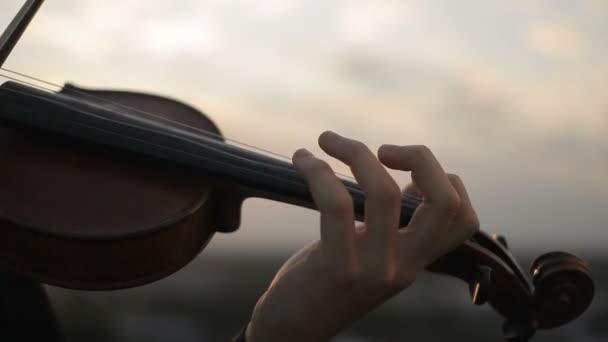 Violin. Violinist playing at sunset. Strings violin and bow.