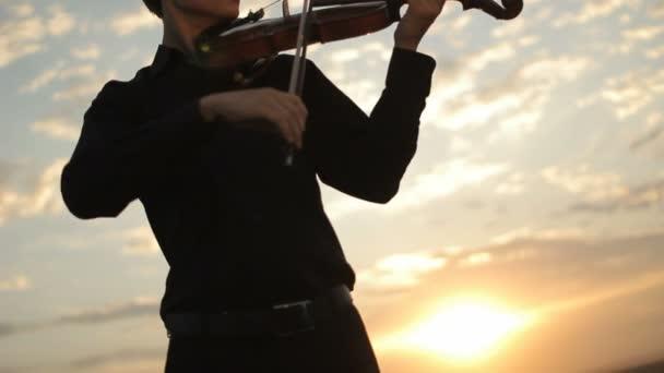 Violinist plays against the sunset. Violin on sunset.