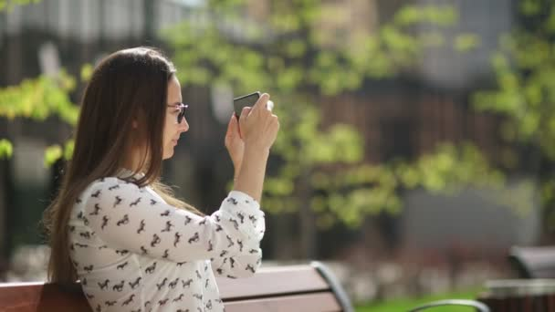 Attractive young girl sitting on the street and photographed on a mobile phone.