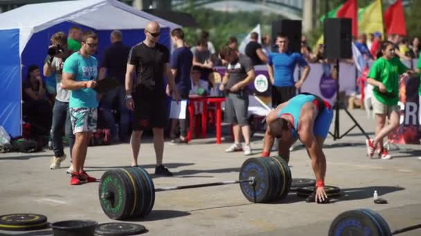 Russia, Novosibirsk, 2016: Bodybuilder puts on weight plate over the bar