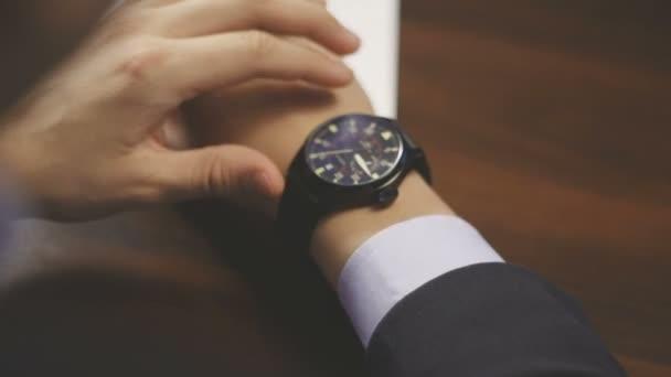 Üzletember ellenőrzési karóra. A kéz az óra