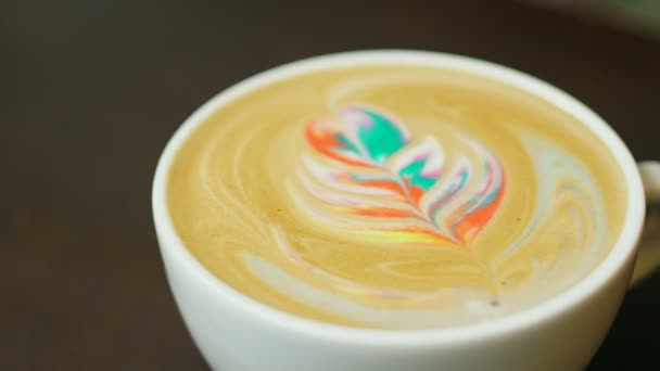 Latte art coffee. Colorful rainbow latte in a white mug.