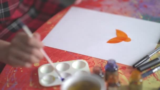 Die Künstlerin malt eine Frauensilhouette. orange Aquarellfarbe.
