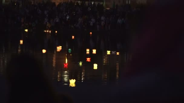 Many people stand along the promenade and look at the water lanterns.