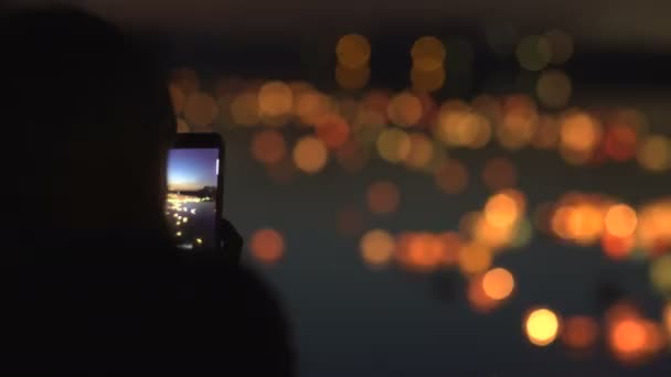 Silhouette of a woman with a phone. Festival of water lanterns.