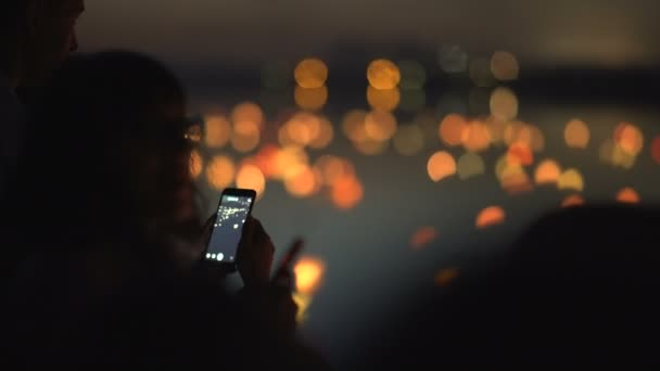 Silhouette of a woman with a phone on a festival of water lanterns