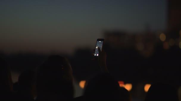 Woman Shooting water lanterns using a mobile phone.