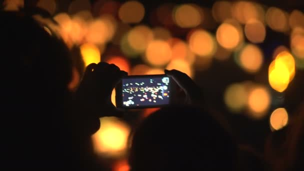 Woman Shooting water lanterns with a mobile phone.