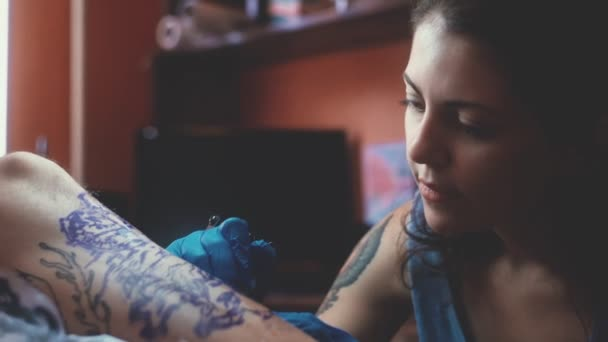 A girl holding a tattoo machine and applied in a pattern on the skin.