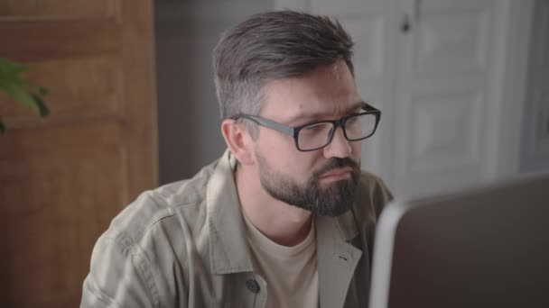 35-year-old man with glasses sitting at a computer in a home interior