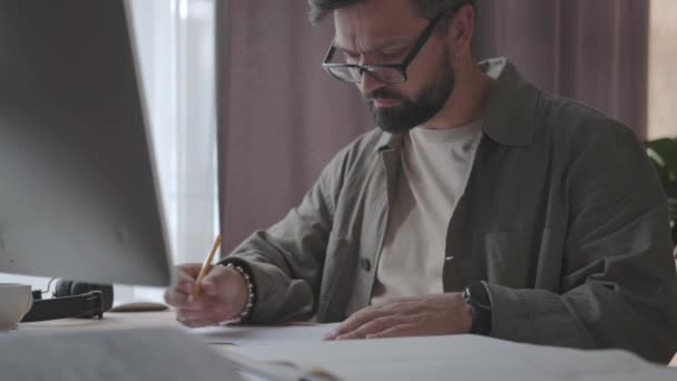 Concentrated man with glasses working on ideas, project at home office