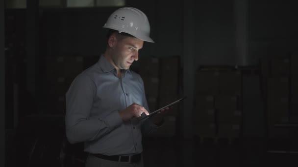 Mann mit Helm und Hemd benutzt Tablet vor dunkler Lagerhalle
