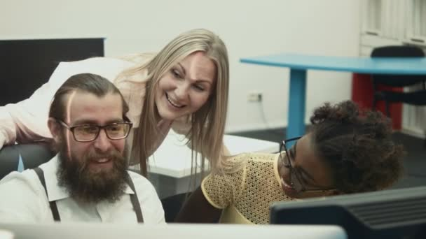 Bearded man and female colleagues talking in office at computer table