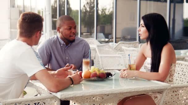 Pohledný muž s přáteli mluvit u stolu