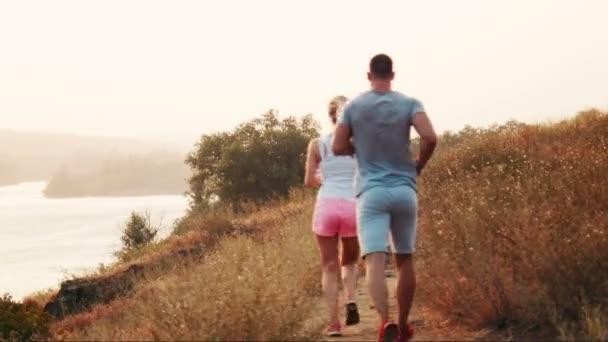 Muž a žena běhání po horské stezce pohled zezadu